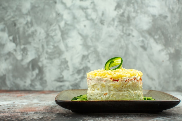 Front close view of tasty salad served with chopped cucumber on mixed color background
