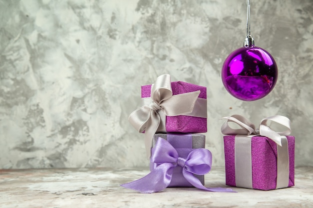 Vista frontale ravvicinata di tre regali di natale per i membri della famiglia e un accessorio decorativo su sfondo di ghiaccio