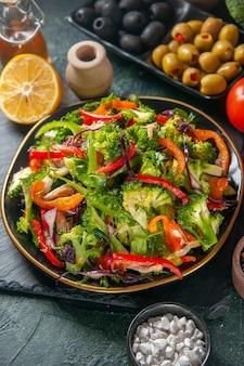 Vista frontale ravvicinata di insalata vegana con ingredienti freschi in un piatto su tavola nera