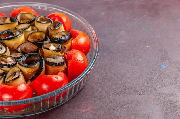 Front close view vegetable meal sliced and rolled tomatoes with eggplants on dark surface