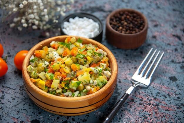 Vista frontale ravvicinata insalata di verdure con condimenti su sfondo blu