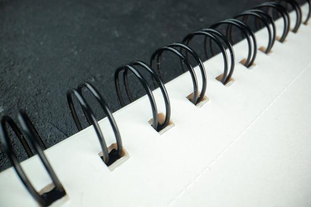 暗いコピーブックの写真の暗闇の正面のクローズビューの白いメモ帳
