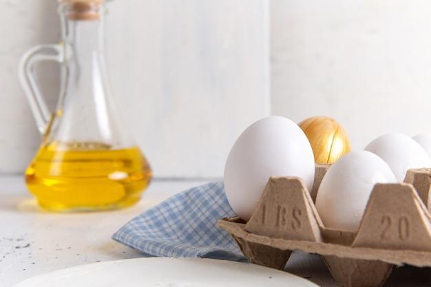 Vista frontale ravvicinata uova intere bianche con quella dorata sul muro bianco