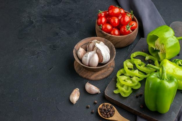 Vista frontale ravvicinata di peperoni verdi tagliati interi tagliati su tagliere di legno pomodori in ciotola aglio su asciugamano di colore scuro su superficie nera