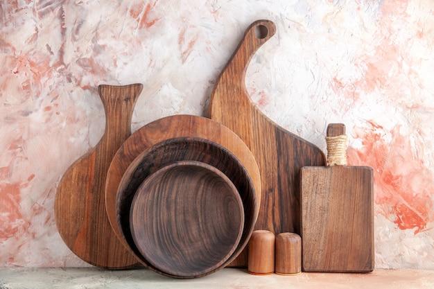 Vista frontale ravvicinata dei taglieri di legno sale pepe pentole sul tavolo colorato