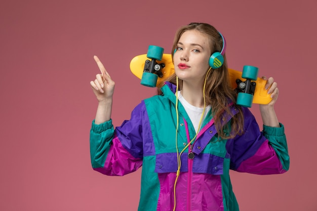 Front close view young attractive female in colored coat listening to music holding skateboard on the pink wall model color female young