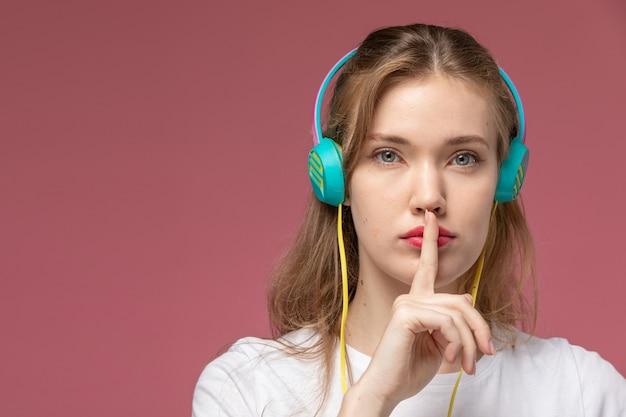 ピンクの壁のモデルの色の若い女性のイヤホンを介して音楽を聴いている白いtシャツの正面のクローズビュー若い魅力的な女性
