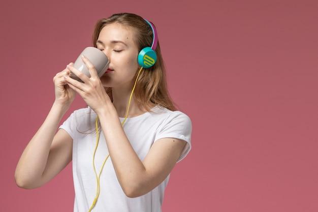 Vista frontale ravvicinata giovane femmina attraente ascoltare musica e bere il tè sul muro rosa modello colore femmina giovane