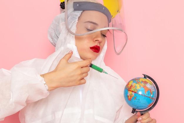 Вид спереди крупным планом молодая красивая женщина в специальном белом костюме в защитном шлеме, вводящая круглый земной шар на розовом