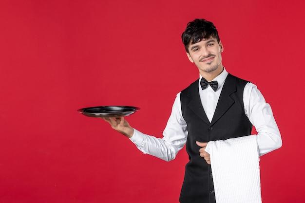 Vista frontale ravvicinata del giovane cameriere sorridente fiducioso e felice in uniforme con farfalla sul collo che tiene vassoio e asciugamano su sfondo rosso
