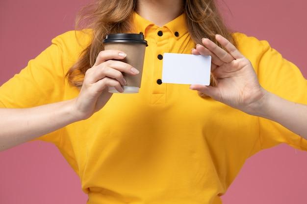 Вид спереди крупным планом молодая женщина-курьер в желтой форме, держащая чашку кофе и белую карточку на розовом фоне, рабочий стол службы доставки униформы