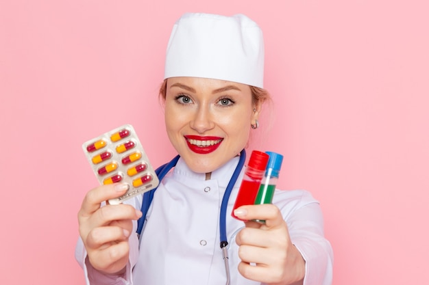 Front close view young female doctor in white medical suit with blue stethoscope holding pills and flasks on pink