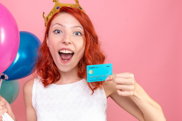 Front close view young female holding colorful balloons and bank card on pink