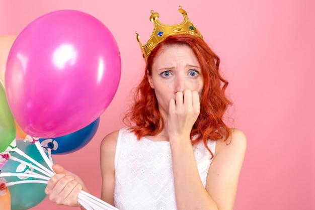 ピンクに神経質なカラフルな風船を保持している正面のクローズビュー若い女性