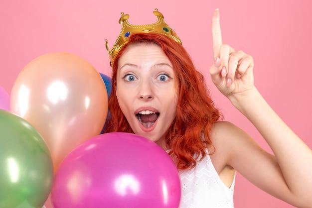 ピンクにカラフルな風船を持っている正面のクローズビュー若い女性