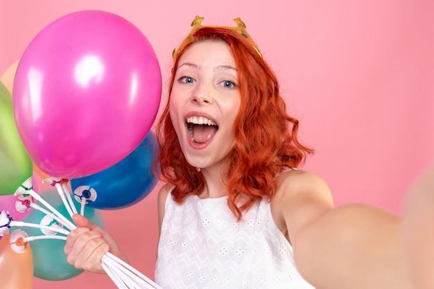 핑크에 기쁨 다채로운 풍선을 들고 전면 닫기보기 젊은 여성 무료 사진