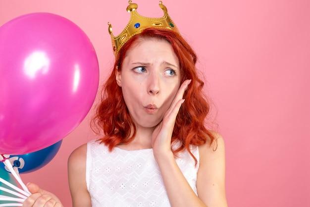 ピンクを心配しているカラフルな風船を保持している正面のクローズビュー若い女性
