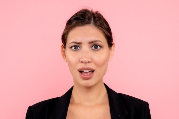 ピンクの背景で混乱している暗いジャケットの正面クローズビュー若い女性