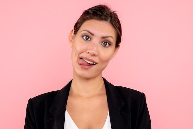 분홍색 배경에 재미 있은 얼굴을 만드는 어두운 재킷에 전면 닫기보기 젊은 여성