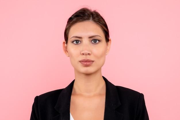 ピンクの背景に暗いジャケットの正面のクローズビュー若い女性