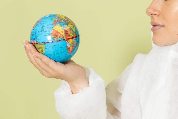 白の特別なスーツと緑の小さな地球を保持している黄色いヘルメットのフロントビューの若い女性