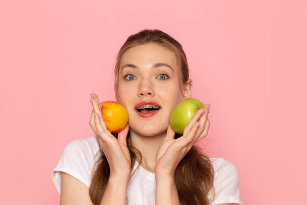 淡いピンクの壁に桃と新鮮な青リンゴを保持している白いtシャツの正面の若い女性