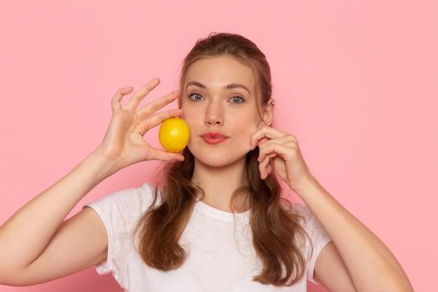 ピンクの壁に新鮮なレモンを保持している白いtシャツの正面のクローズビュー若い女性
