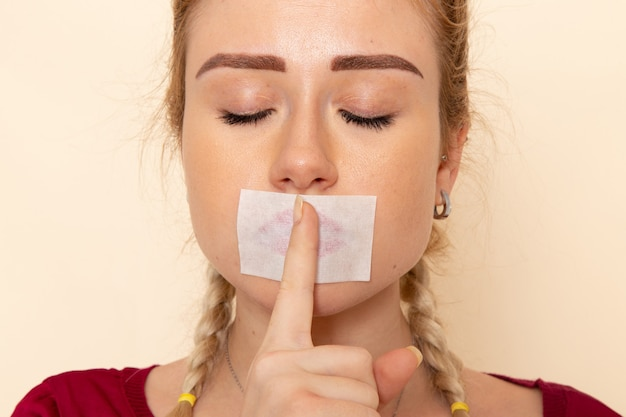 Front close view young female in red shirt with tied mouth showing silence sign