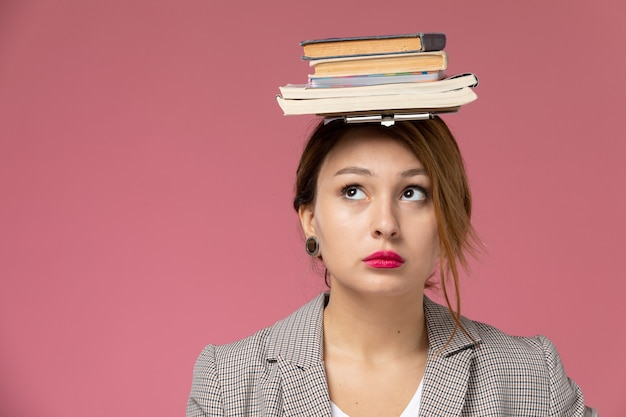 Front close view young female student in grey coat posing and holding books with her head on pink background lessons university college study