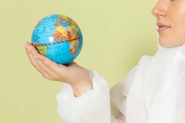 Front close view young female in white special suit and yellow helmet holding little earth globe on green