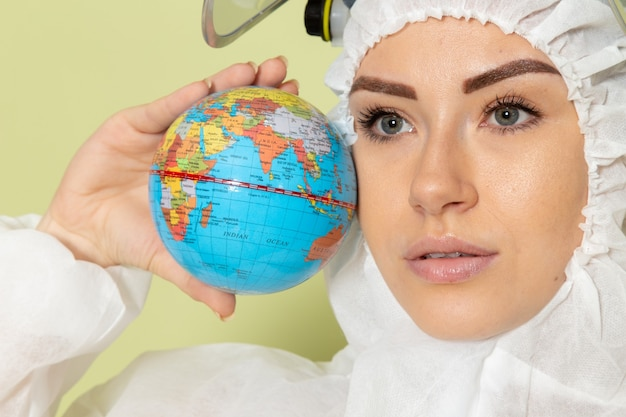 Front close view young female in white special suit and yellow helmet holding little globe on green