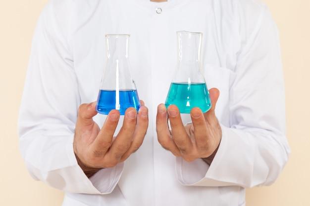 Chimico maschio giovane vista ravvicinata frontale in abito speciale bianco che tiene piccoli boccette con soluzioni su parete crema scienza esperimento chimica scientifica