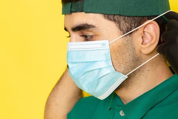 Front close view young male courier in green shirt green cap wearing sterile mask