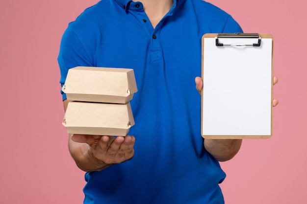淡いピンクの壁にメモ帳付きの小さな配達食品パッケージを保持している青い制服ケープの正面の若い男性の宅配便、均一なサービスを提供