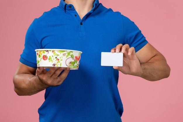 薄いピンクの壁に白いカードと丸い配達ボウルを保持している青い制服ケープの正面の若い男性の宅配便、制服配達サービス