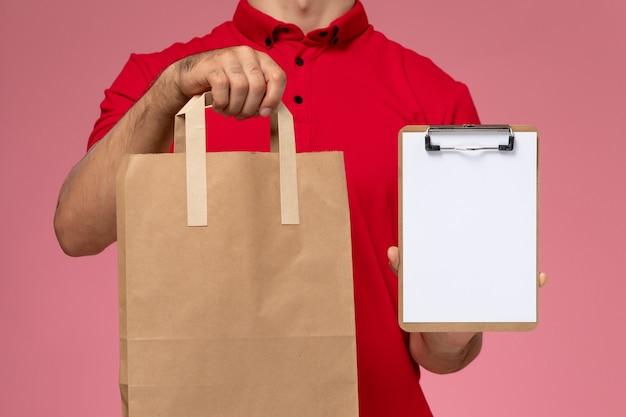 Вид спереди крупным планом молодой мужчина-курьер в красной униформе держит пакет с едой и блокнот на розовой стене