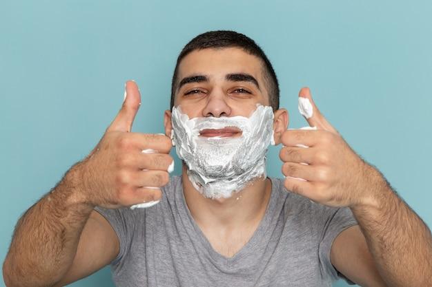 Vista ravvicinata frontale giovane maschio in maglietta grigia che copre il viso con schiuma bianca per la rasatura sul muro blu ghiaccio barba schiuma da barba maschio