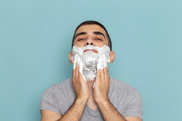 Vista ravvicinata anteriore giovane maschio in maglietta grigia che copre il viso con schiuma bianca per la rasatura sulla parete blu ghiaccio barba rasoio da barba