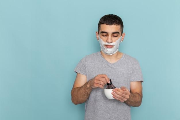 Vista ravvicinata frontale giovane maschio in maglietta grigia con schiuma bianca sul viso sul muro blu ghiaccio barba schiuma da barba maschio