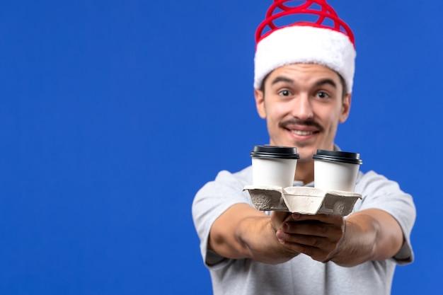 Tazze di caffè della tenuta del maschio giovane di vista ravvicinata anteriore sul nuovo anno maschio di emozione della parete blu