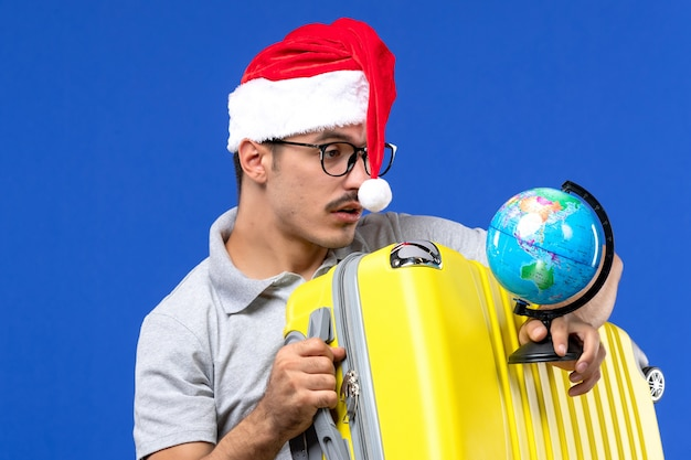 Front close view young male holding globe and yellow bag on blue wall plane vacation trip