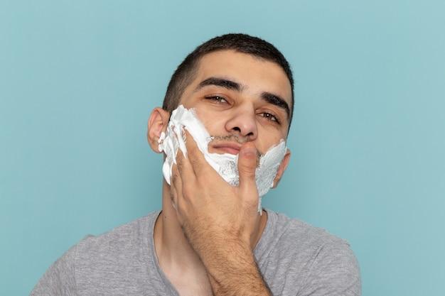 正面を見る灰色のtシャツを着た若い男性が、氷のように青い机のひげの泡のかみそりを剃るために白い泡で顔を覆っている