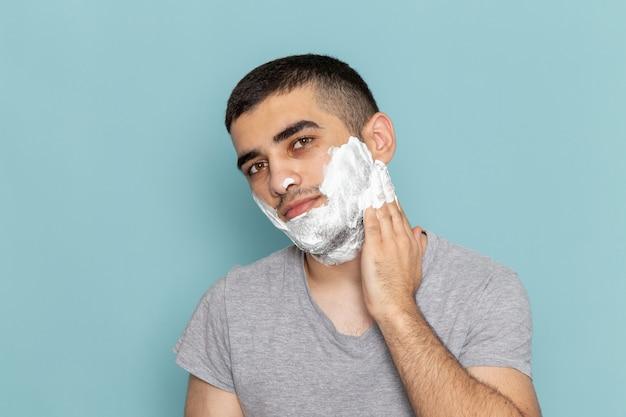 正面を見る灰色のtシャツを着た若い男性が、アイスブルーの壁にひげを剃るために白い泡で顔を覆っているひげの泡の髪のかみそりのひげそり