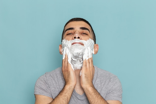 正面を見る灰色のtシャツを着た若い男性が、氷のように青い壁のひげかみそりを剃るために白い泡で顔を覆っている