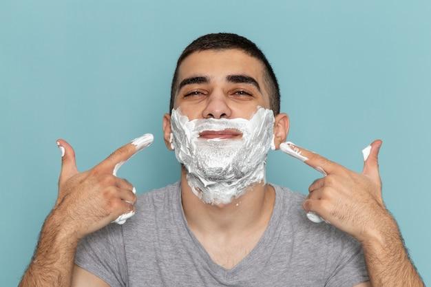 正面を見る灰色のtシャツを着た若い男性が、アイスブルーの机のひげの泡のかみそりを剃るために白い泡で顔を覆っている