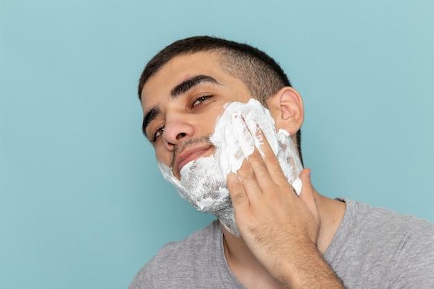 正面を見る灰色のtシャツを着た若い男性が、氷のように青い壁のひげを剃るために白い泡で顔を覆っています。