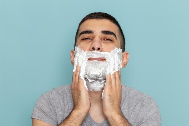 正面を見る灰色のtシャツを着た若い男性が、氷のように青い壁のひげの泡のかみそりのひげそりを剃るために白い泡で顔を覆っている