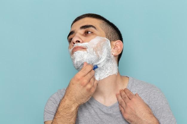 正面のクローズビュー灰色のtシャツを着た若い男性がアイスブルーの壁にかみそりでひげを剃っているひげの泡を剃っている男性