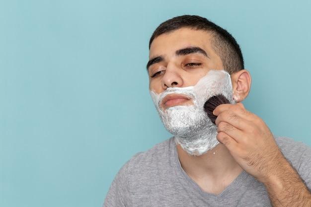 正面の拡大図灰色のtシャツを着た若い男性の顔に白い泡があり、氷のように青い壁のひげの泡を剃っている男性に固定している