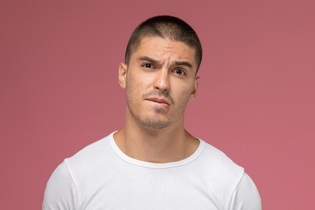 ピンクの机の上の困惑した表情でポーズをとって白いtシャツでフロントのクローズアップビュー若い男性